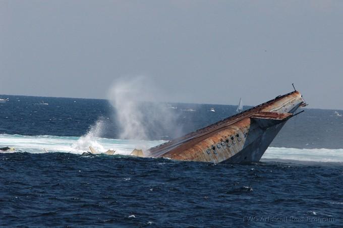 A brown ship hull sinks beneath a blue ocean surface under a blue sky