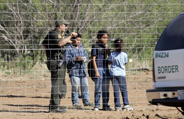 people by fence at US southern border