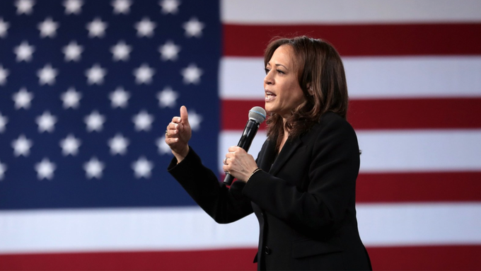 Sen. Kamala Harris speaks in front of the American flag at the Poor People's Campaign forum